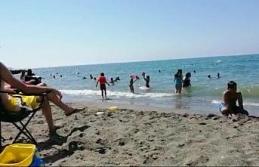 Çocuklar, kumsalın anne babalar denizin tadını çıkarıyor